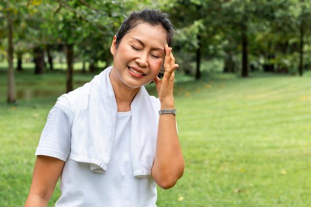 朝。公園で運動中のシニア女性のアジアの頭痛。 Premium写真