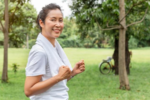 笑みを浮かべて、公園でジョギング中年のアジアの女性。 Premium写真