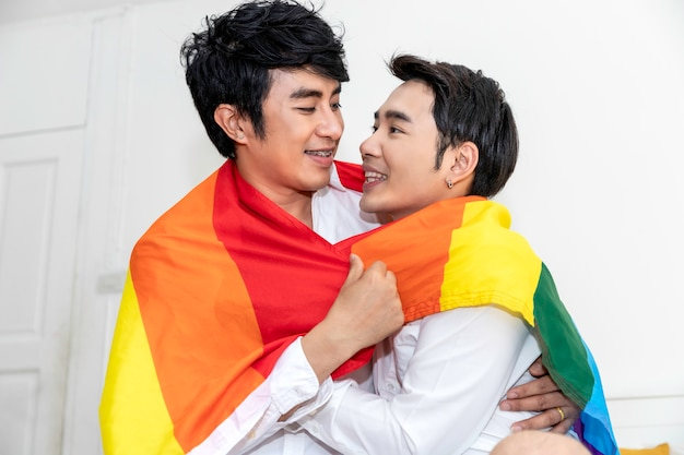 アジアの同性愛カップルの抱擁と寝室でプライドフラグと手を握っての肖像画 Premium写真