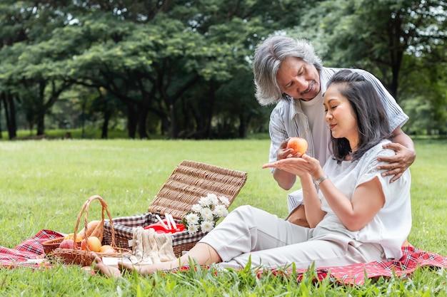 アジアのシニアカップルがリラックスして公園でピクニック。妻は私の夫にリンゴを与えます。 Premium写真