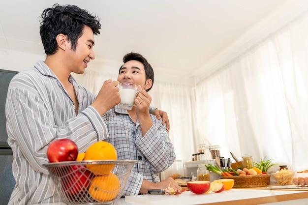 アジアの同性愛者のカップルがキッチンで牛乳を飲む Premium写真