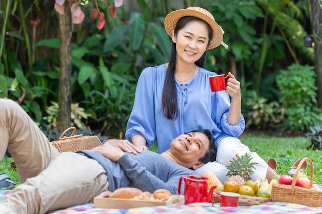 午前中に。公園でコーヒーとピクニックを飲むアジアのシニアカップル。 Premium写真