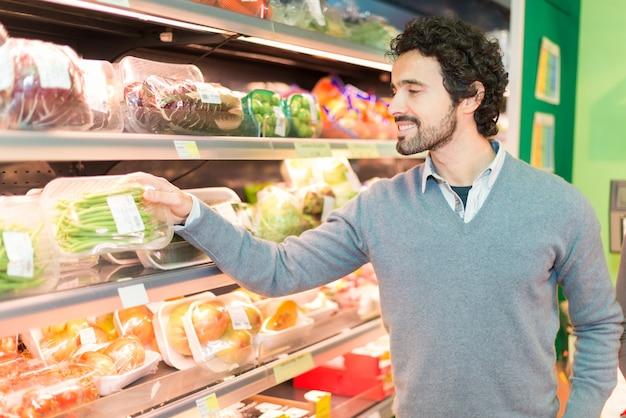 食料品店で野菜を拾う男 Premium写真