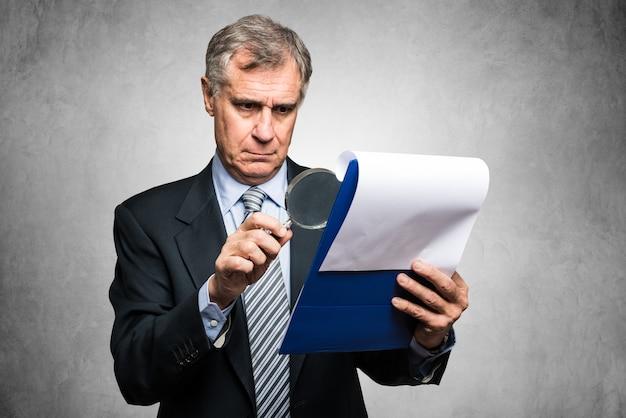 Бизнесмен с помощью увеличительной линзы для анализа контракта Premium Фотографии