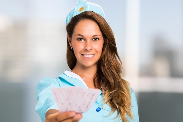 Портрет улыбающейся стюардессы холдинг билеты Premium Фотографии