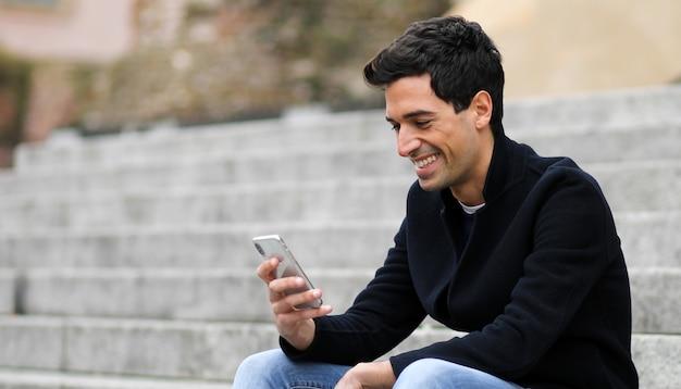屋外の階段に座っているスマートフォンを使用して若い男 Premium写真