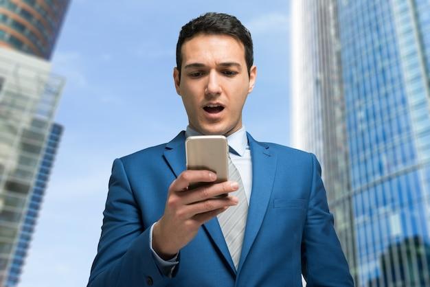 Удивленный бизнесмен, глядя на свой мобильный телефон Premium Фотографии