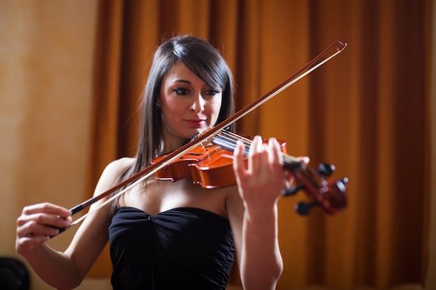 彼女のバイオリンを弾く若いミュージシャン女性 Premium写真