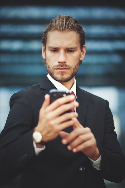 Молодой предприниматель, с помощью своего телефона Premium Фотографии