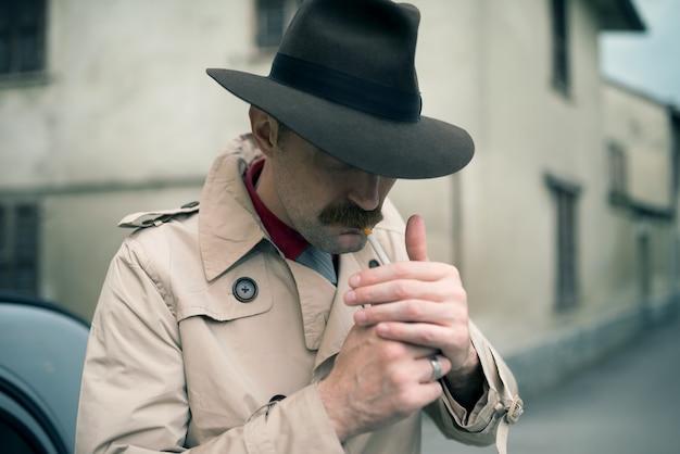 Мобстер закуривает сигарету во время ожидания перед своей винтажной машиной Premium Фотографии