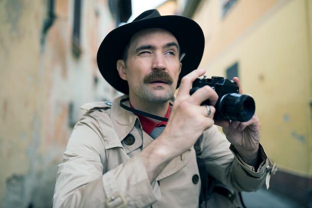 Фотограф шпион или папараццо, человек, использующий камеру на городской улице Premium Фотографии