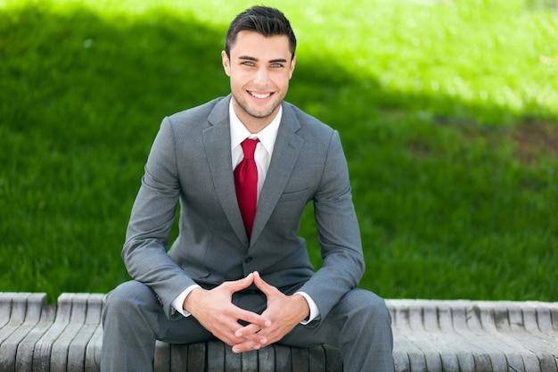 屋外のベンチに座っているビジネス男の肖像画 Premium写真