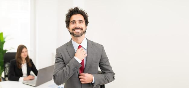彼のネクタイを調整するハンサムな実業家の肖像画 Premium写真