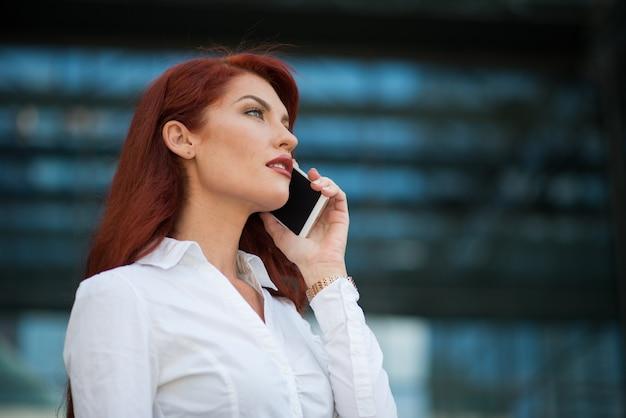 彼女のオフィスの前で彼女の携帯電話を使用してビジネスの女性 Premium写真