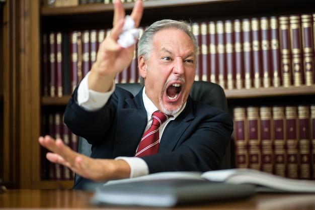 怒っているビジネスの男性がしわくちゃのドキュメントを解き放つ Premium写真