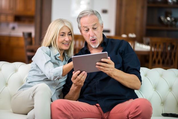デジタルタブレットを使用して成熟したカップル Premium写真