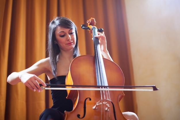 チェロを弾く若い女性 Premium写真