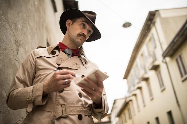 Детектив, пишущий на тетради, в то же время стоя на старой стене Premium Фотографии