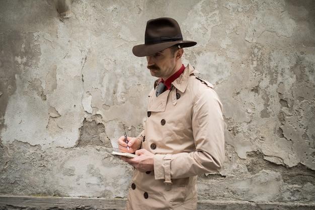Детектив, пишущий на тетради, в то же время стоя у старой стены Premium Фотографии