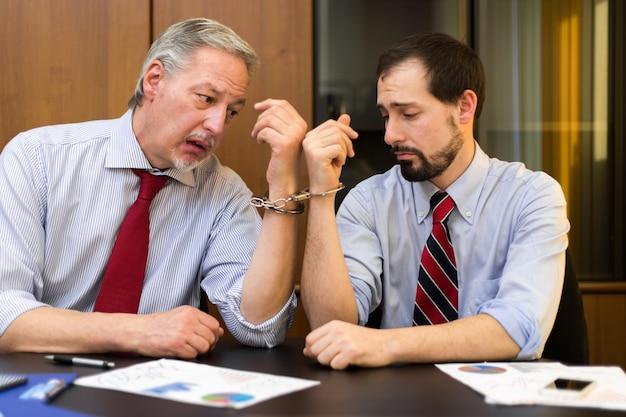 Двух бизнесменов заставили работать вместе наручниками Premium Фотографии
