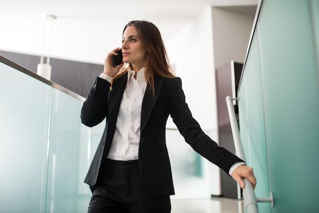 Деловая женщина разговаривает по телефону во время прогулки по лестнице в ее офисе Premium Фотографии