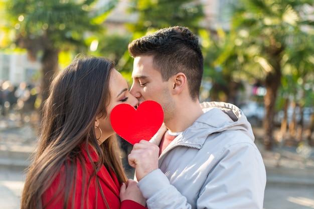 Пара, охватывающая их поцелуй с сердцем Premium Фотографии