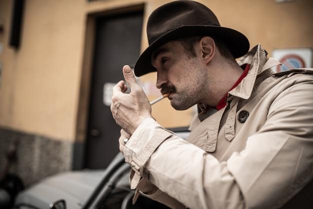 Мобстер закуривает сигарету во время ожидания перед винтажным автомобилем Premium Фотографии