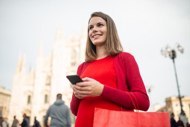 彼女のスマートフォンを使用しながら街を歩いてショッピング女性 Premium写真