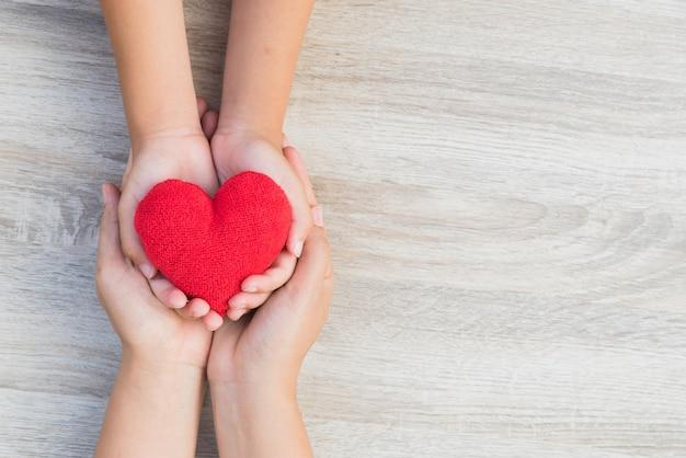 大人と子供の手は、木製の背景に手作りの赤い心臓を保持しています。 Premium写真