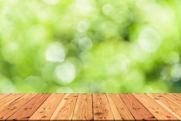 木製のテーブルとぼかし自然ツリー緑色の背景春や夏のコンセプト。 Premium写真
