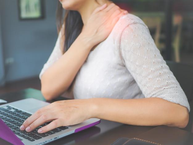 彼女の肩の痛みを持って手を持つクローズアップの女性。オフィス症候群 Premium写真