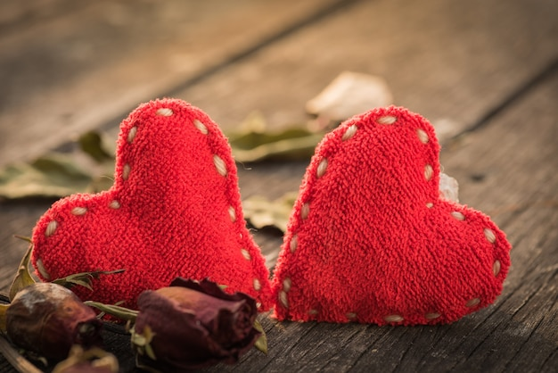 Сушеная красная роза, мертвая красная роза с двумя красными сердцами на деревянном фоне Premium Фотографии