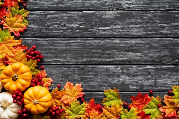 秋のカエデはカボチャと古い木製の背景に赤い果実と葉。 Premium写真