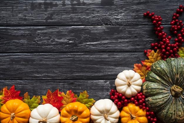 秋のカエデはカボチャと古い木製の背景に赤い果実と葉。感謝祭の共同 Premium写真