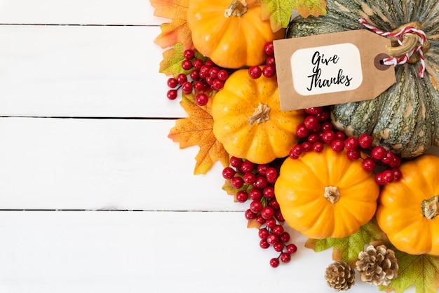 木製の背景にカボチャと赤い果実と秋の葉が残っています。感謝祭のコンセプト Premium写真