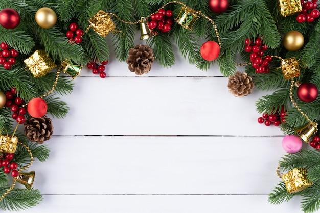 Рождественская подарочная коробка красные шары с еловыми ветками, сосновые шишки, красные ягоды на деревянной спинке Premium Фотографии