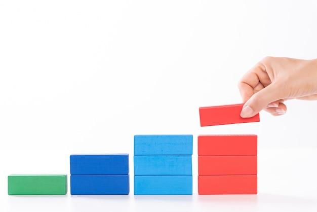 建物の成功のコンセプトは、女性の手が階段の形をした木製のブロックを置きます。 Premium写真