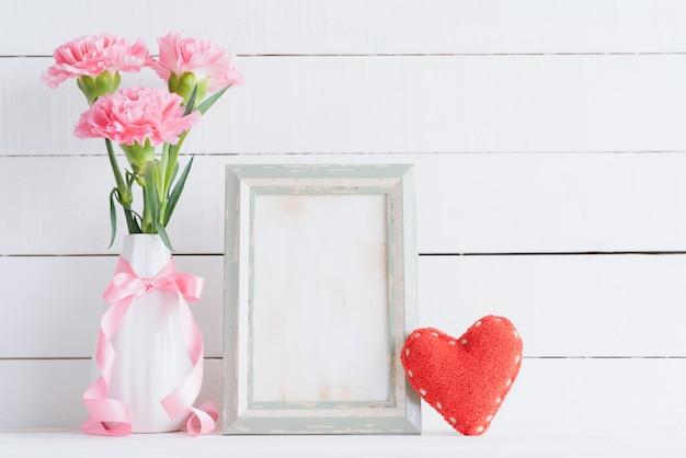 バレンタインの日と愛の概念。木製の背景の上に花瓶にピンクのカーネーション。 Premium写真