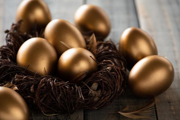 イースター、おめでとう!イースターエッグの黄金の巣と羽の木製の背景 Premium写真