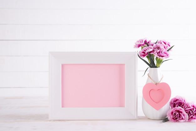 白い木製のテーブルの上に花瓶にピンクのカーネーションの花と白の写真フレーム。 Premium写真