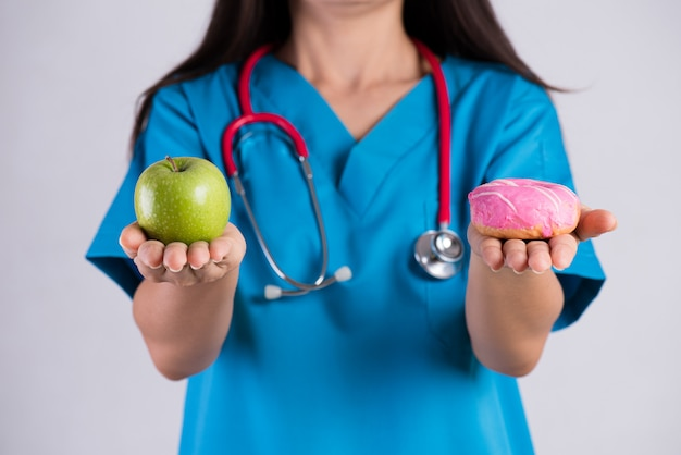 ドーナツと青リンゴを持つ医師女性手 Premium写真