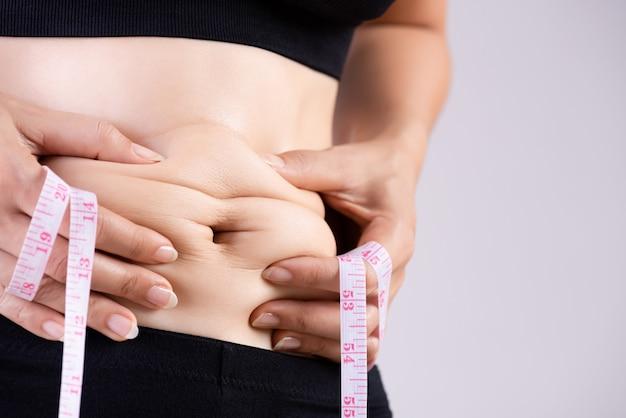 Толстая женщина рука избыточный жир живота с измерительной ленты. Premium Фотографии