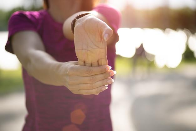 公園で走る前に手を伸ばす女性ランナー。 Premium写真