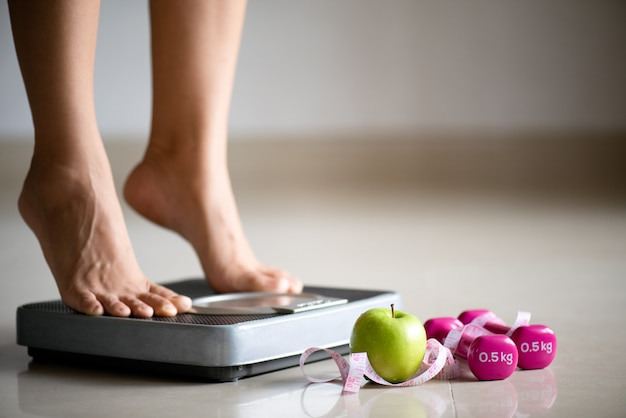 測定テープで体重計を踏む女性の脚 Premium写真