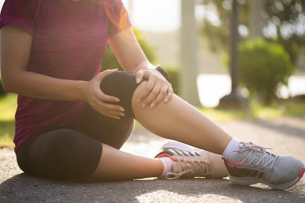 女性ランナーは、公園で膝に痛みを感じます。屋外運動のコンセプト。 Premium写真