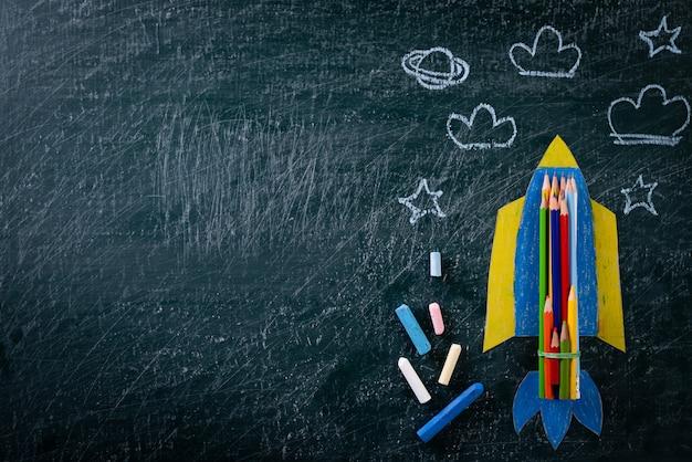 教育または学校概念に戻る。黒板に塗られた紙のロケット Premium写真