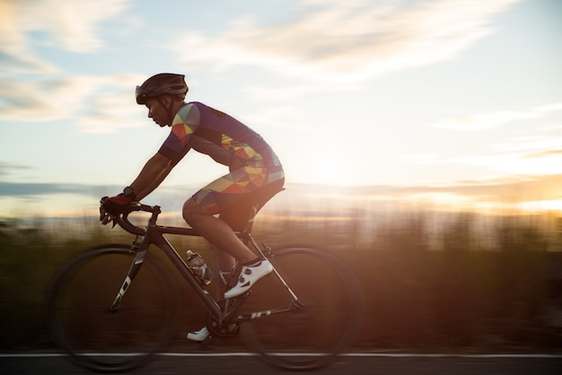朝、スポーツコンセプトの男サイクリングロードバイク Premium写真