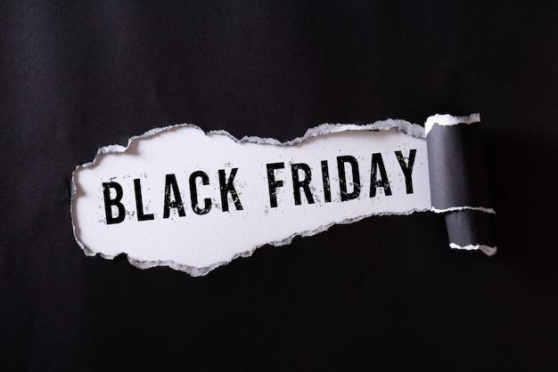 Черная рваная бумага и текст черная пятница на белом. Premium Фотографии