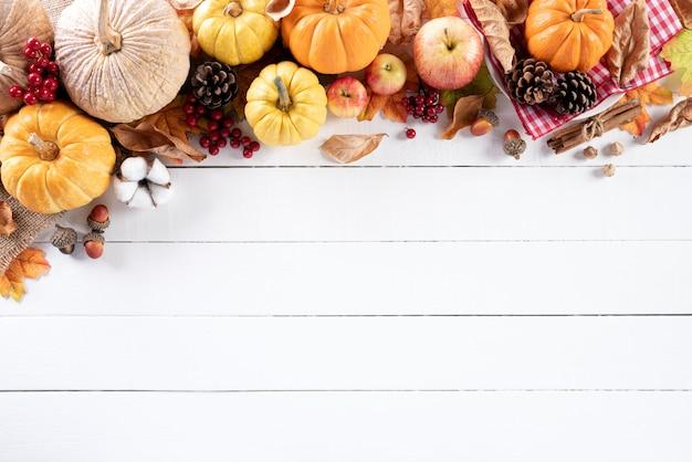 白い木製の背景に秋のカエデの葉。感謝祭の日。 Premium写真