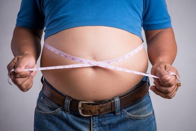 測定テープと非常にタイトなジーンズの太りすぎまたは太った成人男性 Premium写真